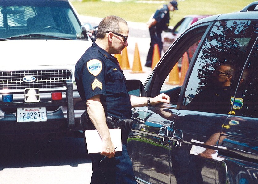 Officer Standing Next to a Vehicle After a Violation